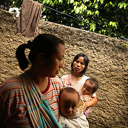 "Dian Dama Yanthi, 32, and her children, Galang, 3, and Gilang Rama, 1, with her friend Sri, 36, and her 7-month-old son Taufan, at Dian's house in Tangerang, on the outskirts of Jakarta, Indonesia, April 19, 2006. Dian had an unsafe abortion and lost her best friend to an unsafe abortion. Both took the traditional medicine ""jamu."" Dian also had a massage from a traditional birthing attendant. Over two million abortions are performed in Indonesia every year, many by unskilled practitioners. Thousands of women survive but often with life-long disabilities. It is said by doctors and activists that a woman dies every hour in Indonesia due to unsafe abortions."