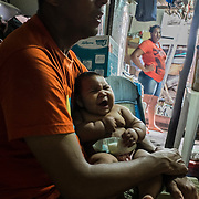 Paulo (49), Maria (20) and their daughter with microcephaly Eduarda Vitoria (5 months) inside their house, a shelter inside the slum of Santa Luzia in Recife, Pernambuco. Both of them are unemployed and extremely poor