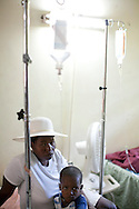 A woman and her son, who is sick with cholera, sit in the pediatric cholera ward at the Hospital Albert Schweitzer on Saturday, October 30, 2010 in Deschapelles, Haiti.