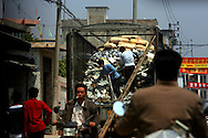 Workers unload electronic waste from trucks as seen from a hidden position inside of a vehicle, in an area where much of the world's electronic waste _ from cell phone chargers to mainframe computers _ ends up in Guiyu and other small towns like it in eastern China, Thursday March 16, 2006. Workers, many of them poorly paid migrants strip, smash and melt down circuit boards, mainly to extract the copper and other precious metals inside. The business has created massive pollution from leaded glass and other toxic materials. China's growing consumption of computers, cell phones and other gadgets poses new challenges, which much of the waste ending up in Guiyu and similar areas now coming from within the country.