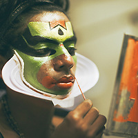 Kumily, Kerala, India: a 'Katakhali' dancer prepares for his performance by applying colorful paint on his face.