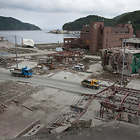 Workers clear the tsunami destruction, caused by the March 11th earthquake and tsunami, in Onagawa, Tohoku region, Japan, on Friday 17th June 2011. There are now fears for the pollution and health risks that this debris now holds, including the releasing into the air of asbestos dust.