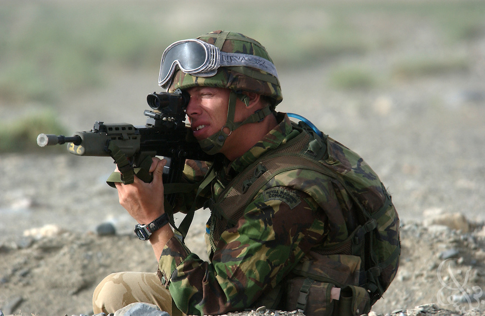 A British Royal Marine of 45 Commando waits in a defensive position for extraction during an eagle vehicle check point (VCP) mission as part of the ongoing Operation Buzzard July 8, 2002 in southeastern Afghanistan. During VCPs, small groups of marines are dropped quickly by helicopters to search random vehicles on dirt roads and trails near the Pakistan-Afghanistan border to deny al Qaeda and Taliban fighters freedom of movement across the region.