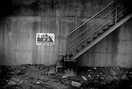 Sign advises people to escape danger by climbing stairs over three storeys to the top of this massive tsunami wall but it would not have been enough to save their lives.  This wall in Toni, Iwate Prefecture, was breached and then toppled by the 11 March 2011 tsunami, Japan.