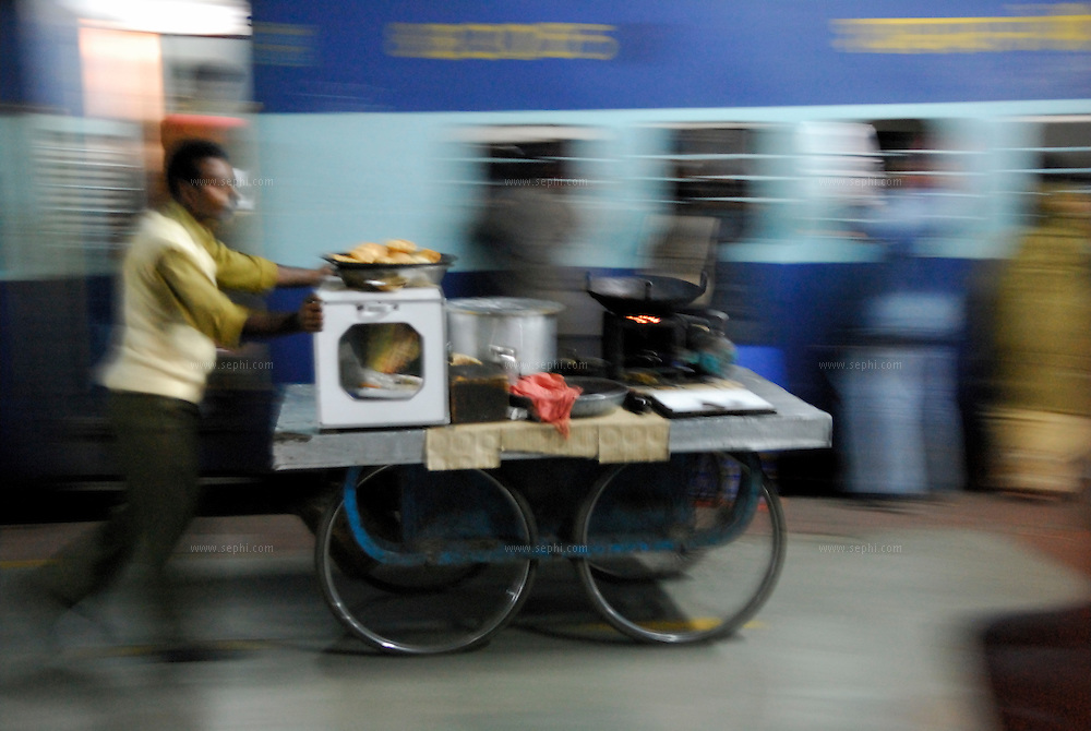 Night time at Haridwar railway station, a hawker pushs his mobile shop along the tracks, offering fresh fried puri to the passengers on the train
