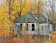 Fall colors on trees outline an old school house in the woods in northern Michigan.