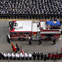 Thousands of firefighters salute as Engine 33 carries the casket of Boston Fire Lt. Edward Walsh, who was killed while fighting a Beacon Street fire, Wednesday, April 02, 2014.