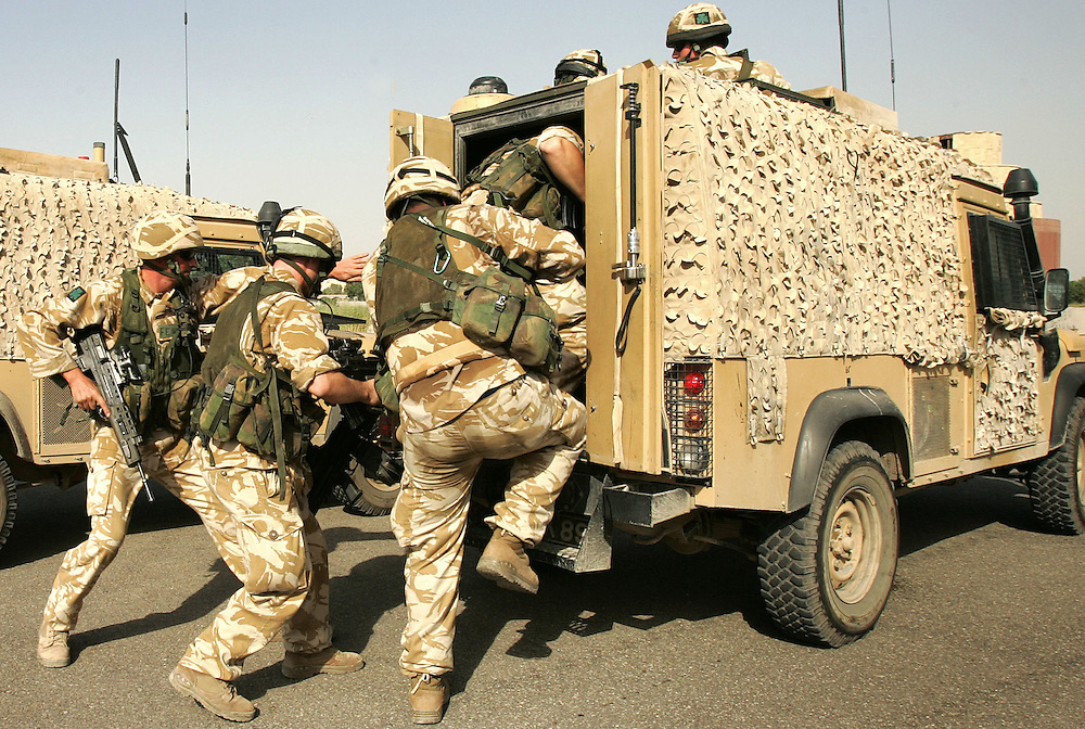 Baghdad, Iraq, 2 Oct 2005. Running 'Route Irish'...Soldiers practice drills essential to staying alive on 'Route Irish'...B Company, 1st Battalion, The Royal Irish Regiment, a tight-knit multi national fighting force make daily escorting runs along ?Route Irish?, the infamous Baghdad Airport road. The 46 man team are all British Army regulars but come from as far afield as Fiji, South Africa and Northern and Southern Ireland. Previous deployments in Kosovo, Sierra Leone and Northern Ireland have equipped them with the valuable skills needed to provide protection for British Forces and materials transiting the world?s most dangerous highway. Due to an increased presence of US forces along the route both in dug in positions and mobile patrols, attacks along the road have slackened, despite this a day rarely passed without an IED (improvised explosive device) being detonated or a small arms attack against coalition forces. ..The convoy attempts to maintain a seclusion ?bubble? around its vehicles for the duration of the journey. Any civilian vehicle that either strays into the bubble or refuses to keep their distance represents a threat and should they ignore the warning blasts on air horns carried in each vehicle the rules of engagement progress from warning shots to use of lethal force. The relative safety of the International Zone offers them an opportunity to decompress between missions. A duty driver ferries soldiers to the ?Liberty Pool?. Once only frequented by Iraq?s Ba?athist elite the luxury swimming pool and gym now fills with troops. Their body armour, helmets and weapons all within easy reach they either soak up the sun or compete with each other in diving competitions. After a daily briefing the troops have access to the ?Mosquito and Camel? bar where they watch TV or play pool and in accordance with the ?2 can rule? are allowed to drink 2 beers per night.
