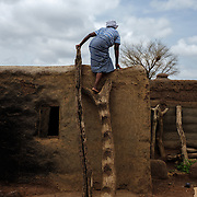 Sophia Bugrmeh ascending a ladder to the roof of her homestead in the village of Berwong in the Upper West Region of Ghana. Grain and shea nuts are often dried on the roof away from the reach of animals, and the roof also provides access to a granary that can not be entered any other way.