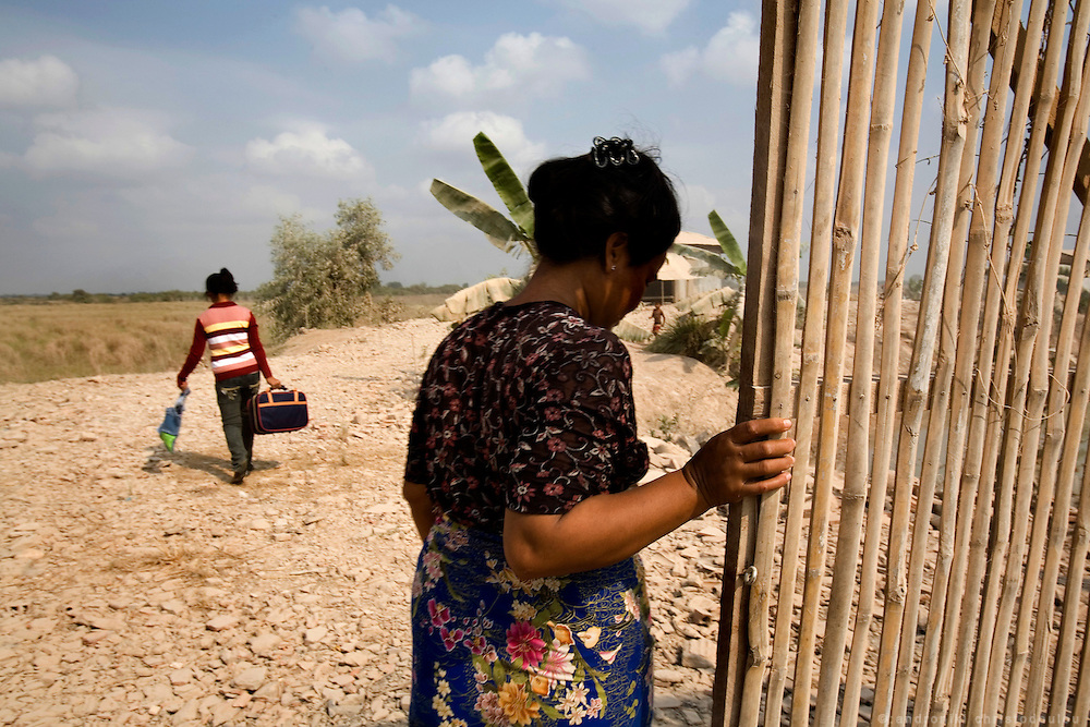 Rady arriving at her outside their home in a remote location outside Sisophon city while her step-mother Jan Cum Saang is closing the gate of the piece of land where they live behind her.