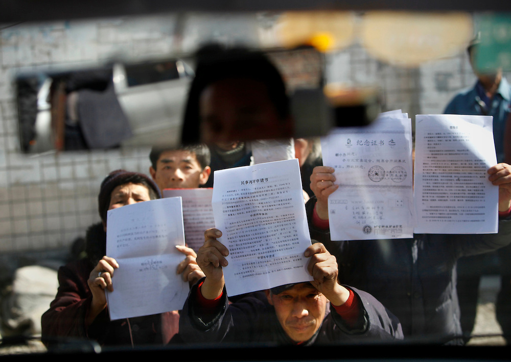 Chinese Petitioners kneel before a car, blocking the vehicle's way, as they beg to display their petition letters near a local government office supposed to receive grievances in  Beijing, China, Friday, Feb.27, 2009.  Police have taken away more than 1,000 petitioners looking to air their grievances ahead of the annual meeting of China's legislature. Widespread frustration with the petition system is simmering and in several recent cases has boiled over, with a handful of people making desperate bids for attention.The peak season for the pilgrimages is the beginning of March, when China's lawmakers gather in the capital for their once-a-year legislative session. In an acknowledgement that the petition system is in crisis, China's Premier Wen Jiabao vowed to improve legal channels for grievances.