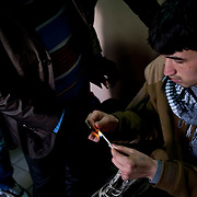 Immigrants are seen burning shoe laces for the use of the string.  Image © Angelos Giotopoulos/Falcon Photo Agency..