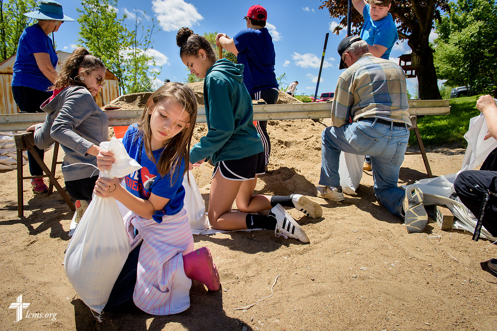 Lilly Peterson (front) joins fellow volunteers from St. John's Lutheran Church, Arnold, Mo., as they fill sandbags to protect church member Ruth Houser's home from rising flood waters on Tuesday, May 2, 2017, in Arnold. With Peterson is (left to right), Gail Pawlitz, Jasmine Baxter, Abbey Gierer, Margaret Bilka, Ray Luebke, Daniel Allen, and Jen Utz. LCMS Communications/Erik M. Lunsford