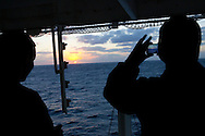 Sailors take pictures of the sunset as seen from on board the USNS Comfort, a naval hospital ship, on its way to help survivors of the earthquake in Haiti on Monday, January 18, 2010 in the Atlantic Ocean off the coast of the United States.