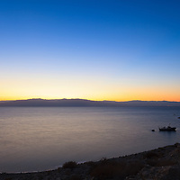 A boat lies at anchor near the public beach at Ein Gedi on the western coast of the Dead Sea shortly before sunrise.