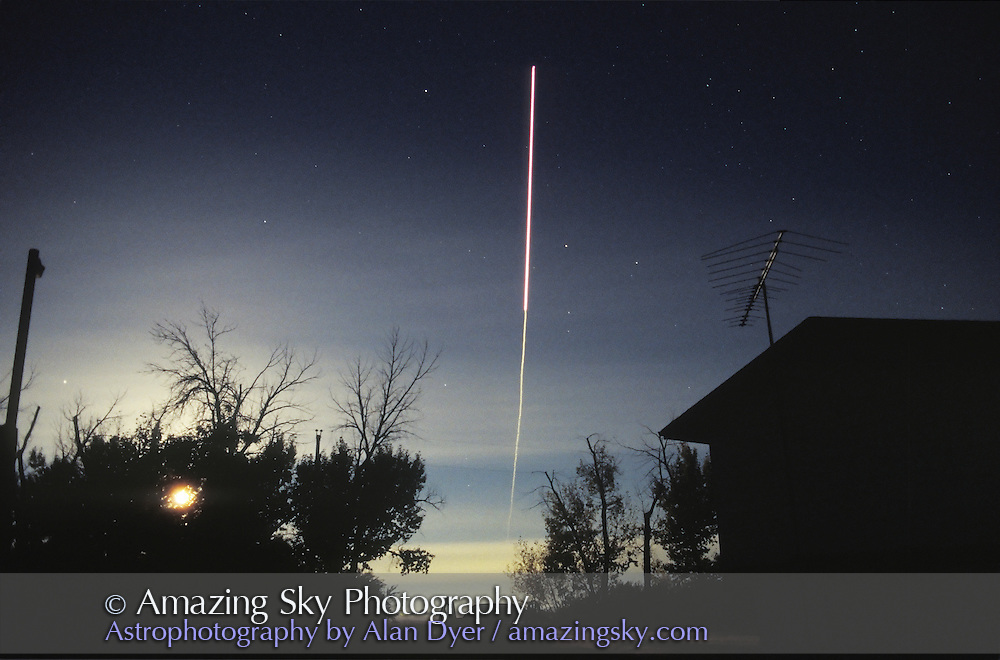Space Shuttle Reentry<br /> September 26, 1996<br /> Reentry of STS79 over Alberta<br /> just before sunrise, with Full Moon light providing illumination, plus dawn twilight.<br /> 28mm lens f/2.8. Roughly 10 sec exposure. Moon is bright light shining thru trees.
