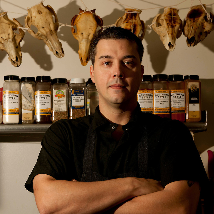 Chef Jason Dodge of Peche Restaurant and Bar stands in front of a spice rack and a collection of skeletal animal skulls. He was the former chef of Vespaio and specializes in European comfort food at Peche.