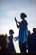 Young woman in numerous group of college students, dressed in blue, uses mobile phone during visit to UNESCO World Heritage, Galle Fort, during Binara Full Moon Poya Day.