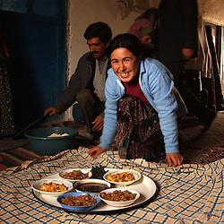 Ali Ipak's daughter Emel, 17, (in blue) offers tea to her father (far left), a neighbor Kazim Kardes, and the mayor of Kutoren Mr Ugur Akdogan  (in suit)   December 13, 2005 in central Turkey, Konya in Kutoren district, about 400 kilometers from Ankara. (Ami Vitale)