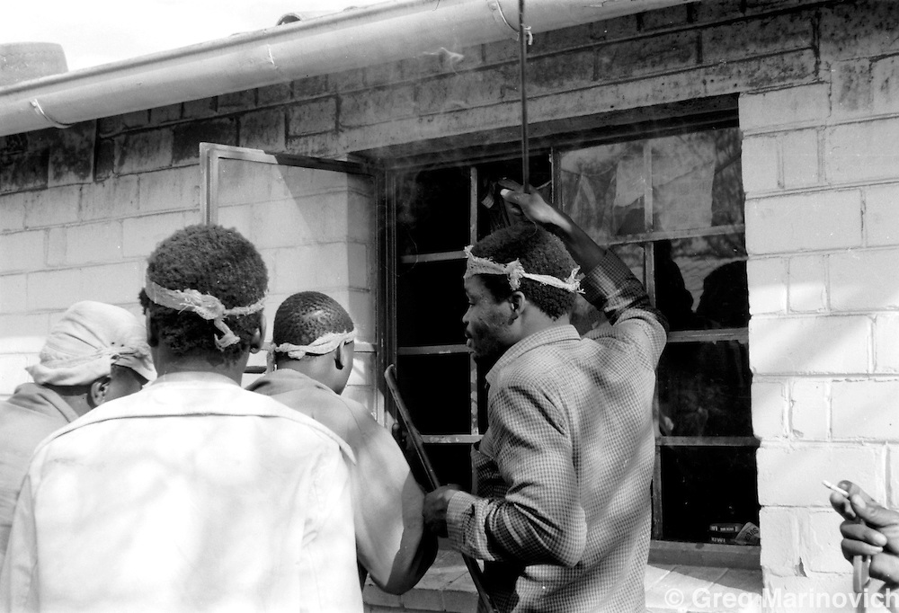Zulu Inkatha supporters burn a hostel next to Phola Park in Tokoza Oct 1990, on the East Rand some 20km East of Johannesburg. The migrant workers' hostel was later destroyed in the clashes between Inkatha Freedom Party supporters and those of the African National Congress. (Photo by Greg Marinovich)