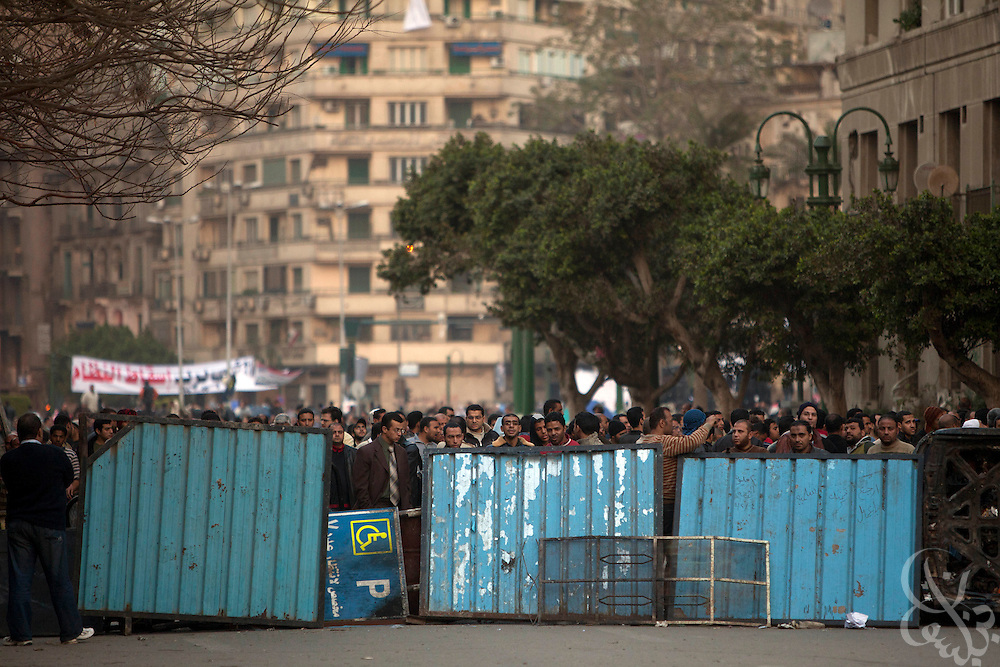Anti-Mubarak protesters stand in position behind barricades meant to keep out pro-Mubarak protesters on the edge of by lines of pro-Mubarak protesters on the edge of Tahrir Square February 02, 2011in Cairo Egypt. Both sides faced off today, battling for control of the square which has been at the center of more than a week of ongoing protests across Egypt. As night fell, there are reports that the Army has ordered everyone in the square to evacuate. .(Photo by Scott Nelson)