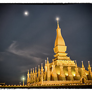 The moon rises over the Laotian temple That Luang in Vientiane.