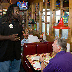 In this photo provided by Pizza Hut, Tampa Bay Buccaneers' offensive lineman Davin Joseph works the lunch crowd for donations to the World Hunger Relief fund at a Pizza Hut in Pinellas Park, Florida October 21, 2008. Joseph joined three other football players across the country in raising funds in the fight against world hunger. (AP Photo/Scott Audette, Pizza Hut)