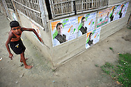 A boy hangs Congress party campaign posters near a polling station during the second phase of voting in parliamentary elections April 23, 2009 in the Muslim dominated town of Mukalmua in the state of Assam, India.  Congress party leaders Rahul Gandhi and Kamal Nath, the commerce minister, and key government allies face Indian voters today in the second round of polling in a five-stage general election.