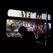 As a passenger dozes, the low winter light illuminates the etched graffiti on window of the N train, crossing the Manhattan Bridge to Brooklyn.