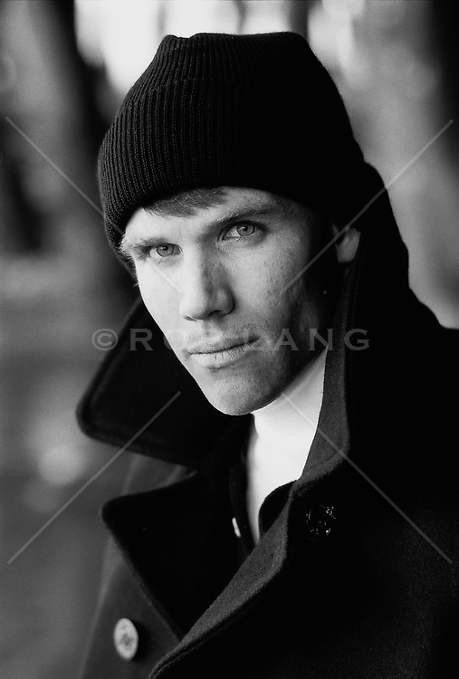 headshot of a man in a hat and peacoat