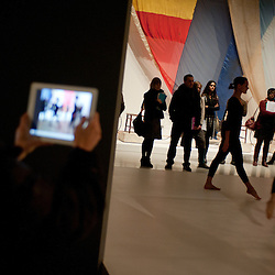 London, UK - 13 February 2013: a visitor takes a picture of dancers performing at the 'The Bride and the Bachelors - Duchamp with Cage, Cunningham, Rauschenberg and Johns' exhibition that opens to the public on 14 February and runs until 9 June 2013 at Barbican. It is the first exhibition to explore Marcel Duchamp's impact on four great modern artists - composer John Cage, choreographer Merce Cunningham and visual artists Robert Rauschenberg and Jasper Johns.
