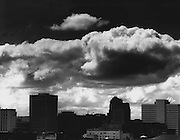 A moisture-laden spring rain cloud hung over the skyline of Seattle. A glint of light  on the horizon lent hope that cloud, too, might have a silver lining. (Josef Scaylea / The Seattle Times, 1967)