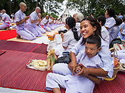 19 JULY 2014 - KHLONG LUANG, PATHUM THANI, THAILAND: A woman and her son relax during a mass ordination at Wat Phra Dhammakaya. Seventy-seven men from 18 countries were ordained as Buddhist monks and novices at Wat Phra Dhammakaya, a Buddhist temple  north of Bangkok, Saturday. It is the center of the Dhammakaya Movement, a Buddhist sect founded in the 1970s and led by Phra Dhammachayo (Phrathepyanmahamuni). It is the largest temple in Thailand. The Dhammakaya sect has an active outreach program that attracts visitors from around the world.    PHOTO BY JACK KURTZ