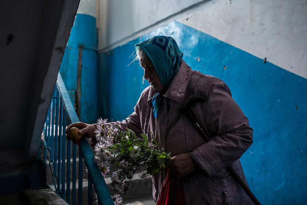 Nadezda Panasyk, 75, walks in the stairwell of her apartment building in the Kievsky district where she lives on Friday, October 17, 2014 in Donetsk, Ukraine. Her building is used by fighters for the Donetsk People's Republic to coordinate efforts to gain control of the Donetsk airport, one of the most heavily contested ongoing battles of the war in Eastern Ukraine. Photo by Brendan Hoffman, Freelance