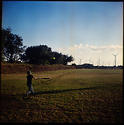 "A young boy plays baseball with the backdrop of wind farms in La Venta, Oaxaca...The Isthmus of Tehuantapec, long a center for indigenous land ownership, is now embroiled in a land dispute over wind farm land...Called ""Mexico's little waist,"" the Isthmus is a wind tunnel that links the Gulf of Mexico to the Pacific through mountain passes at the narrowest part of Mexico. The geographical funnel makes it one of the windiest places in North America and for a decade wind energy companies have been jostling to acquire land to power the likes of Coca-Cola and Wal Mart."