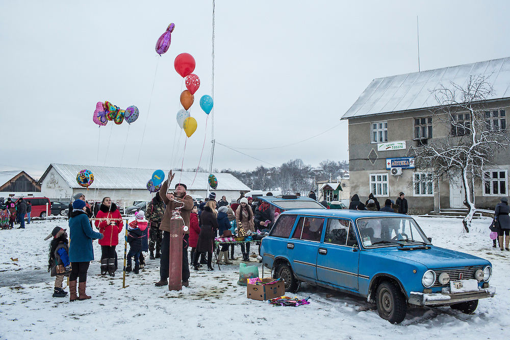 A vendor sells balloons during celebrations of the Malanka Festival on Thursday, January 14, 2016 in Krasnoilsk, Ukraine. The annual celebrations, which consist of costumed villagers going in a group from house to house singing, playing music, and performing skits, began the previous sundown, went all night, and will last until evening.