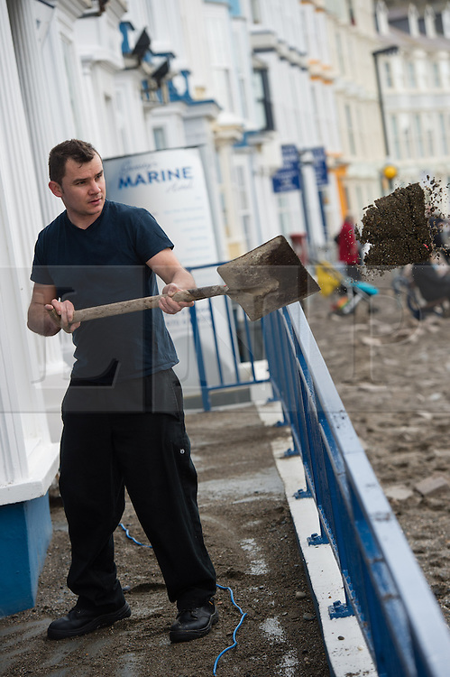 &copy; London News Pictures. 07/01/2014. Aberystwyth, UK.<br /> Workmen and residents begin the long process of clearing debris and damaged on the seafront at Aberystwyth, Wales, caused by a storm which battered the East coast of the UK and Ireland. Photo credit: Keith Morris/LNP