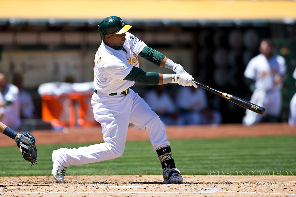 OAKLAND, CA - MAY 26:  Yoenis Cespedes #52 of the Oakland Athletics hits a home run off of Drew Smyly #33 of the Detroit Tigers (not pictured) during the third inning at O.co Coliseum on May 26, 2014 in Oakland, California. The Oakland Athletics defeated the Detroit Tigers 10-0.  (Photo by Jason O. Watson/Getty Images) *** Local Caption *** Yoenis Cespedes