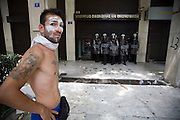 A protester stands infront of masked police guarding an entrance to the Ministry of FInance.  The MPs in parliament prepare to debate new austerity measures required for the EU and IMF bail-out package.  Athens turned into a war zone with many arrests and tear gas thrown by the police. Image © Angelos Giotopoulos/Falcon Photo Agency