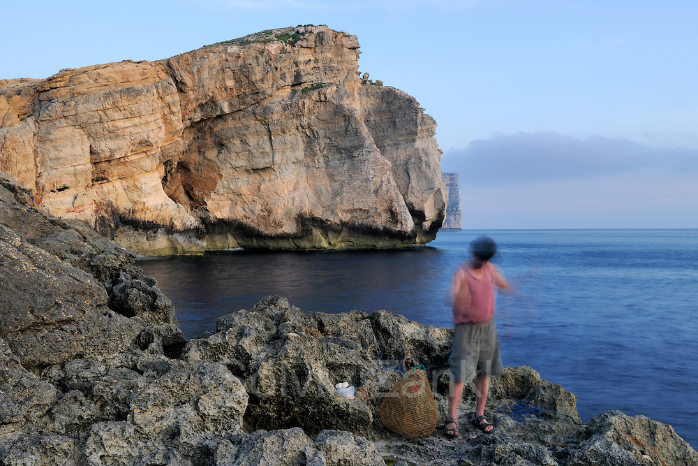Maltese fisher with fishing trap, Fungus Rock in the background