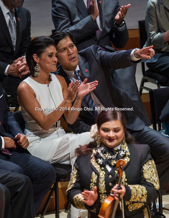 Democratic Sen. Kevin de Leon who was sworn in as President Pro Tempore of the Senate, and his daughter Lluvia Carrasco, gesture to supporters Wednesday, October. 15, 2014, in Los Angeles, California.  De Leon has been sworn in as the first Latino to head the California Senate in more than a century with an expensive and out-of-the-ordinary soiree in downtown Los Angeles. The Wednesday night ceremony was held at Walt Disney Concert Hall with an estimated price tag of $50,000, unlike previous, usually low-key ceremonies at the state Capitol.<br />  (Photo by Ringo Chiu/PHOTOFORMULA.com)