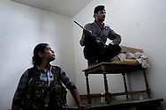 """SYRIA, ALEPPO : Engizek (R) the Kurdish woman leader of the """"Popular Protection Units"""" (YPG) stands near by a comrade fighter inside a building in the majority-Kurdish Sheikh Maqsud district of the northern Syrian city of Aleppo, on April 16, 2013. ALESSIO ROMENZI"""