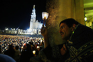 Faithful hold candles during a candlelight vigil at the Catholic Fatima shrine in central Portugal 12 May 2005. Thousands of pilgrims converged on Fatima to celebrate the anniversary of the first apparition of the Virgin Mary to three shepherd children on 13 May 1917.PHOTO PAULO CUNHA/4SEE