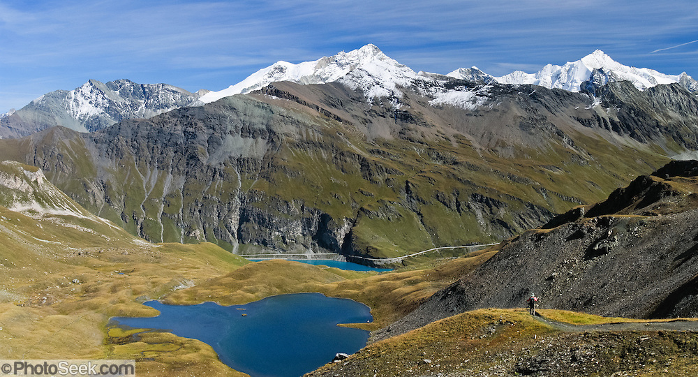 Across from Garde de Bordon peak (center 3310 meters), descend from Col du Torrent to Val de Moiry, Lac des Autannes (2686 meters), and blue-green Lake Moiry in Valais (Wallis) canton, Switzerland, on the High Route (Chamonix-Zermatt Haute Route), Pennine Alps, Europe. Panorama stitched from 2 overlapping images.