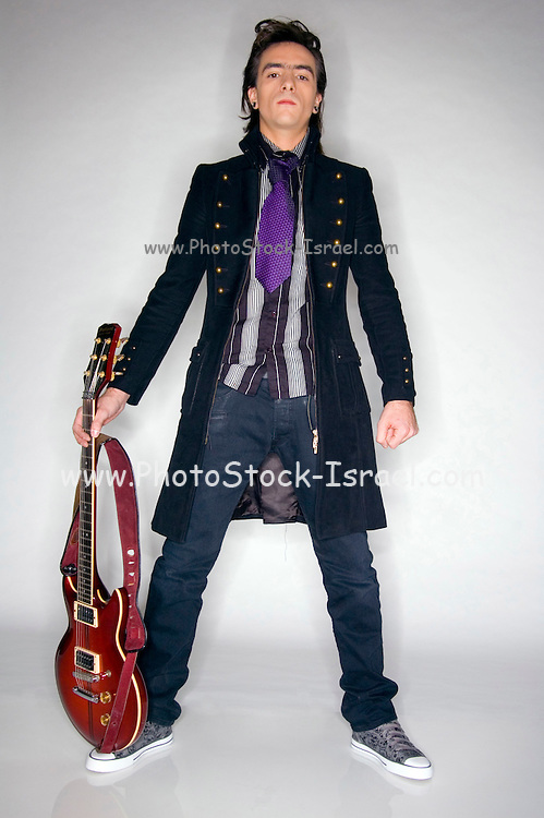 Young male Caucasian in his early 20s in Gothic style clothes playing an electric guitar full body shot. MR