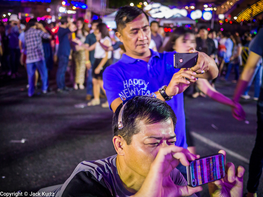 "31 DECEMBER 2012 - BANGKOK, THAILAND:  Men photograph their families with their iPhones at the New Year's Eve party and countdown in the Ratchaprasong intersection in Bangkok. The traditional Thai New Year is based on the lunar calender and is celebrated in April, but the Gregorian New Year is celebrated throughout the Kingdom, especially in larger cities and tourist centers, like Bangkok, Chiang Mai and Phuket. The Bangkok Countdown 2013 event was called ""Happiness is all Around @ Ratchaprasong."" All of the streets leading to Ratchaprasong Intersection were closed and the malls in the area stayed open throughout the evening.   PHOTO BY JACK KURTZ"