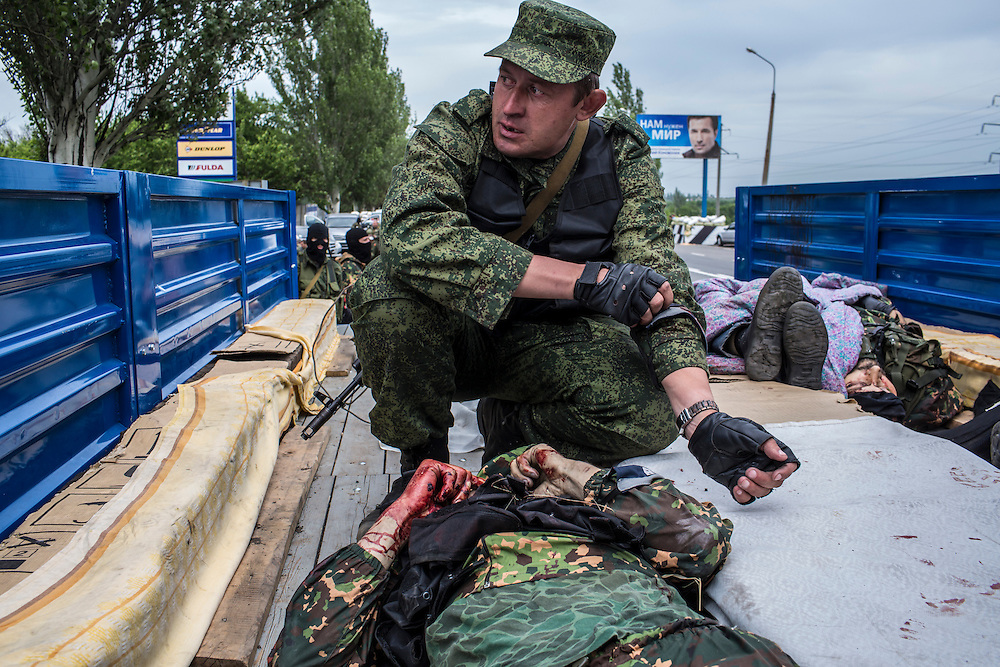 PISKY, UKRAINE - MAY 23: A member of the pro-Russia Vostok Battalion folds the arms of a dead colleague on May 23, 2014 in Pisky, Ukraine. At least eight people between the two sides, including one civilian, were killed in an early morning firefight when the Donbass Battalion, a pro-Ukraine militia, attacked a Vostok Battalion checkpoint in the nearby town of Karlivka. (Photo by Brendan Hoffman/Getty Images) *** Local Caption ***