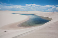 One of the Lençois do Maranhão lagoons during the Winter season. The sand filters the water from the rain and creates clear water lagoons. Lençois do Maranhão, a 155 thousand hectares National Park in the state of Maranhão, Brazil. In the middle of this sea of sand on a oasis called 'Queimada dos Britos' lives a small community.  The legend says that the founder Manuel Brito, after running away from home due to a drought that was scorching his homeland, he ended up settling down in the only non-sandy portion of the Lençois.
