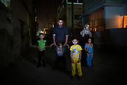 Ammar Mohammed Alajrab, 30, from the Bab Amur suburb of Homs, Syria, pictured with his family outside the building in which they rent a basement apartment, in Al Mafraq, Jordan, which they moved into after fleeing from Syria.<br /> <br /> The governor of Homs would collect money for the regime, they limit everything the people need, there are no generators, no water tanks, there is no electricity, but the Alawite community has everything. We were oppressed, we couldn't even mention then name of Bashar [Assad], then we saw the revolution in Tunis and Egypt and we were inspired by them.  Everyday we used to protest against the regime and the corruption, 300 people or more! When the regime saw this they sent soldiers and tanks to stop the gathering of people. They started to break into houses and interrogate the people and look for weapons. We were protesting in Homs at the same time as those in Deraa. <br /> <br /> People used to protest around the main clock in the center of Homs, then one night, at 1:30am, the army fired on the crowd, to this day no-one knows how many were killed. They [Syrian Army] entered my house one night at 4am, they broke the door down and ordered us to stand and face the wall. They had a list and they compared all the names with ours, they asked us, &quot;who are the protestors?&quot; They said I must co-operate and then hit me with a gun, they told us to get out of our own home. They stole from the abandoned houses: TVs, washing machines, food, money, jewellery. In the morning we found that everyone on the list had been taken away. <br /> <br /> After this we didn't feel secure. We didn't leave the house for twenty days, we were scared because there were checkpoints everywhere. My brother was detained and there was no sign of him for fifteen days, then we found him wandering. He had been tortured, for 1 month he didn't speak, he is here with me now but he has a disorder and cannot speak properly. After twenty days we left Homs because it was