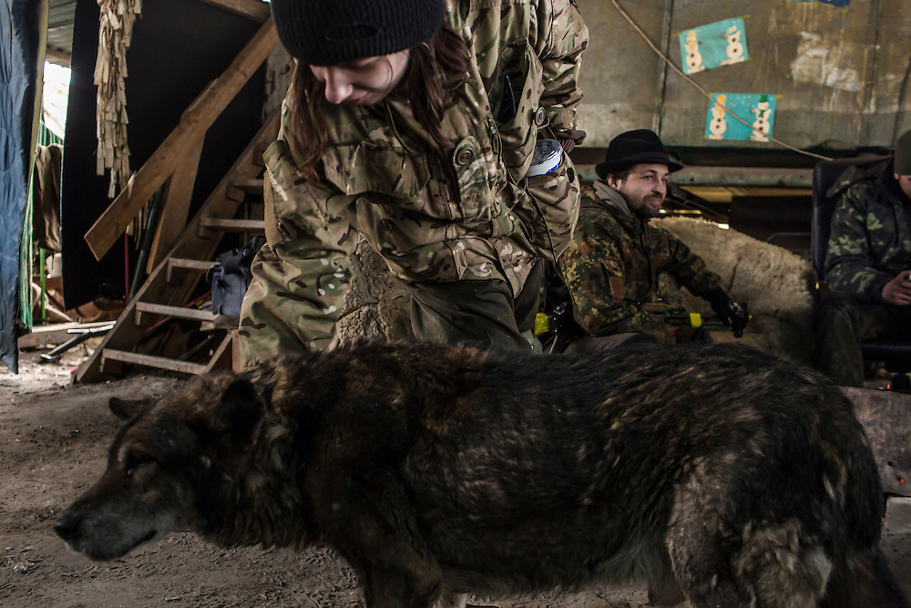 PERVOMAISKE, UKRAINE - MARCH 19, 2015: A female fighter with the pro-Ukrainian Dnipro-1 battalion pets a dog at one of the group's bases known as The Bridge near ongoing battles for the town of Pisky in Pervomaiske, Ukraine. CREDIT: Brendan Hoffman for The New York Times